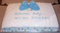 photo of a cake that has baby booties on top