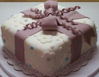 photo of a cake that looks like a present, complete with a bow on top made of fondant
