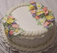 photo of a cake decorated with a basket weave pattern and royal icing flowers